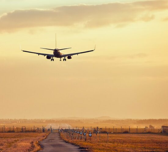 Lądujący samolot przy zachodzie słońca